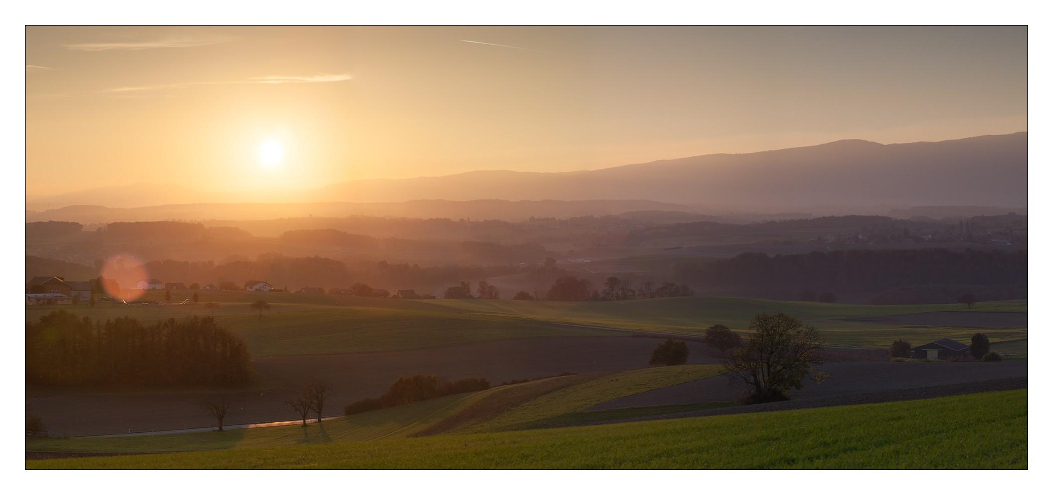 Couché de soleil sur la plaine brumeuse.